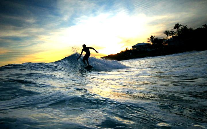 Surfista pegando onda no por do sol